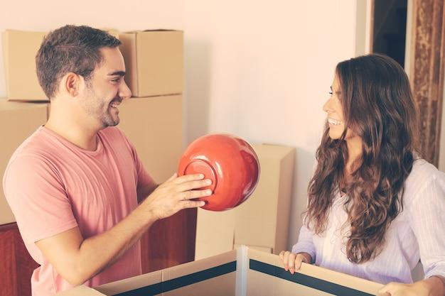Alegre joven y mujer moviendo y desembalando cosas, saliendo del objeto de la caja de cartón abierta