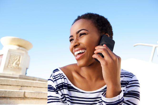 Alegre joven mujer negra escuchando celular