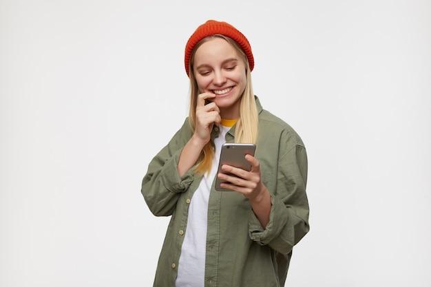 Alegre joven mujer rubia de pelo largo con maquillaje natural sosteniendo el teléfono móvil en la mano levantada y sonriendo mientras revisa las redes sociales, aislado en azul