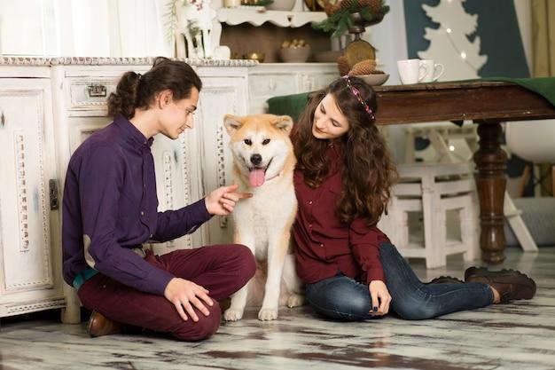 Alegre joven pareja abraza y besa a un perro de raza akita inu
