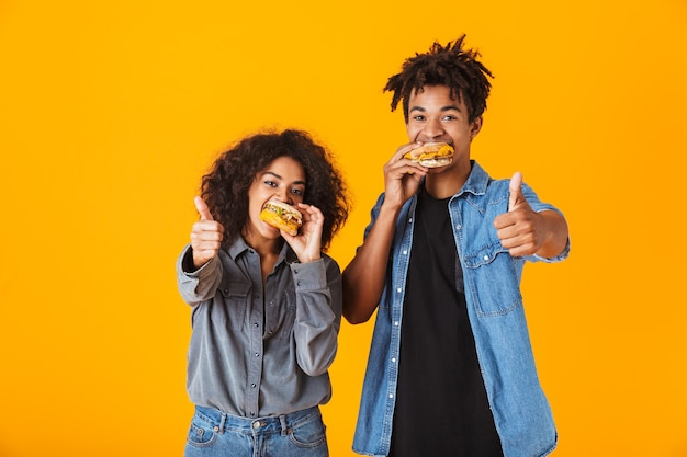 Alegre joven pareja africana que se encuentran aisladas, comiendo hamburguesas, pulgares arriba