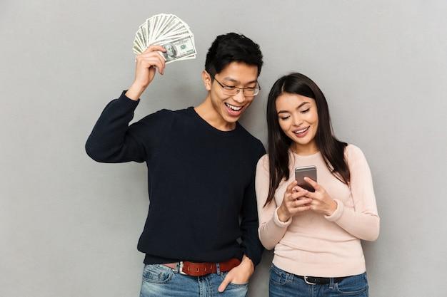 Alegre joven pareja amorosa asiática con dinero y teléfono móvil.