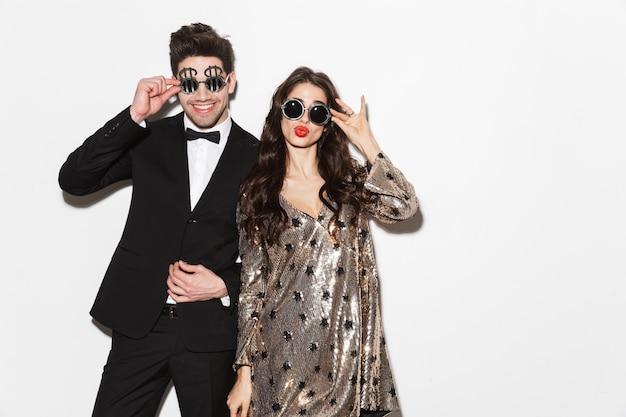 Alegre joven pareja elegantemente vestida celebrando la fiesta de año nuevo aislado sobre blanco