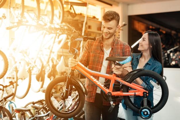 Alegre joven pareja elige niños bicicleta en la tienda.