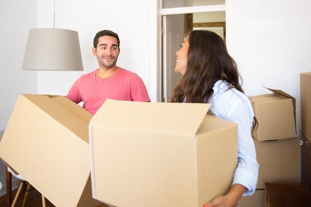 Alegre joven pareja latina llevando cajas de cartón en su nuevo piso, hablando y riendo