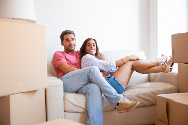 Alegre joven pareja latina sentada en el sofá entre paquetes de cartón en el nuevo apartamento,