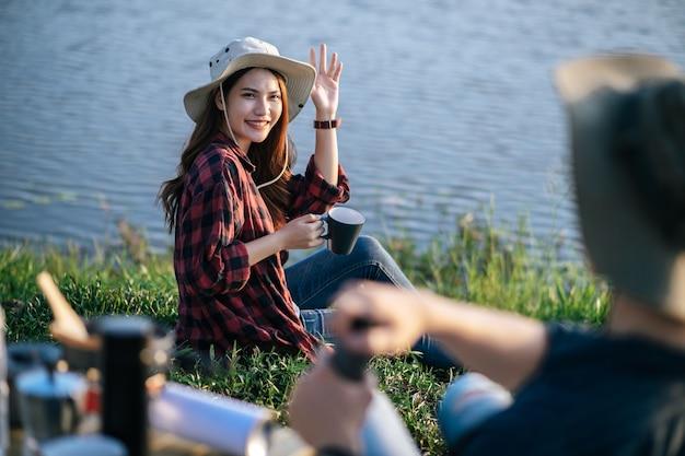 Alegre joven pareja de mochileros con sombrero de trekking sentado cerca del lago con juego de café y haciendo molinillo de café recién hecho mientras acampa en vacaciones de verano