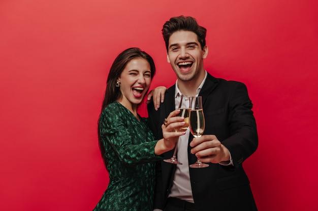 Alegre joven pareja de personas en trajes de vacaciones, sonriendo, sosteniendo copas con champán y mirando al frente aislado en la pared roja
