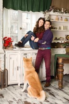 Alegre joven pareja posando sentada en una cómoda con un perro de raza akita inu