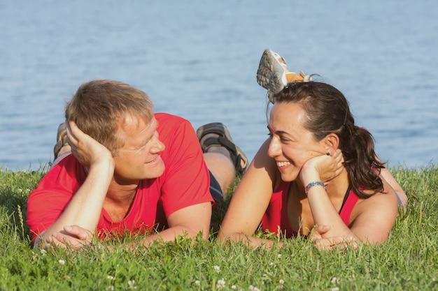 Alegre joven pareja se superpone en la orilla del lago balaton en hungría