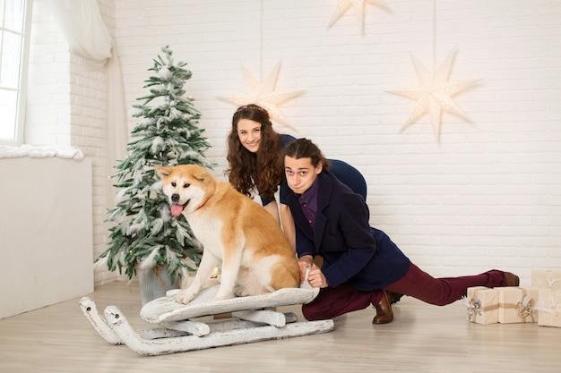 Alegre joven pareja en un trineo con un perro en decoraciones navideñas