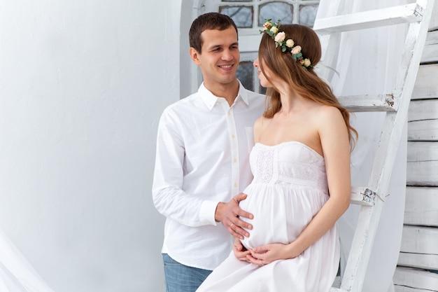 Alegre joven pareja vestida de blanco de pie en casa