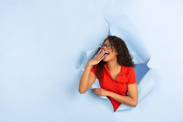 Alegre joven posa en fondo de agujero de papel azul rasgado, emocional y expresivo