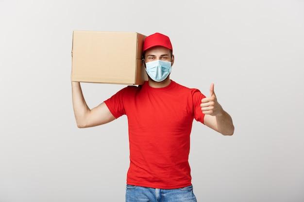Alegre joven repartidor guapo sosteniendo una caja de cartón