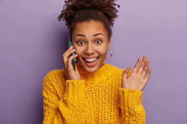 Alegre joven rizada habla por teléfono, feliz de escuchar buenas noticias, hace gestos durante la conversación, levanta la palma, usa aretes y suéter amarillo, disfruta de la conversación informal, aislado sobre fondo morado