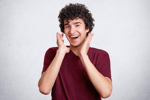 Alegre joven rizado que está de buen humor, se ríe alegremente mientras escucha una broma agradable, sonríe, posa contra el muro de hormigón blanco, usa una camiseta informal. concepto de personas, felicidad y positividad