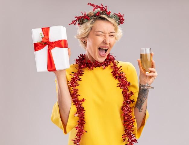 Alegre joven rubia con corona de navidad y guirnalda de oropel alrededor del cuello sosteniendo una copa de champán y paquete de regalo gritando con los ojos cerrados aislados sobre fondo blanco.