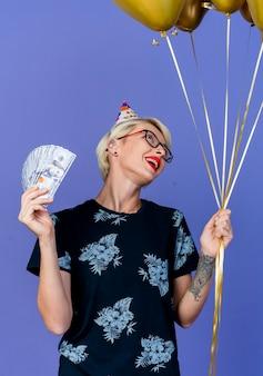 Alegre joven rubia fiestera con gafas y gorra de cumpleaños sosteniendo globos y dinero mirando globos aislados sobre fondo púrpura