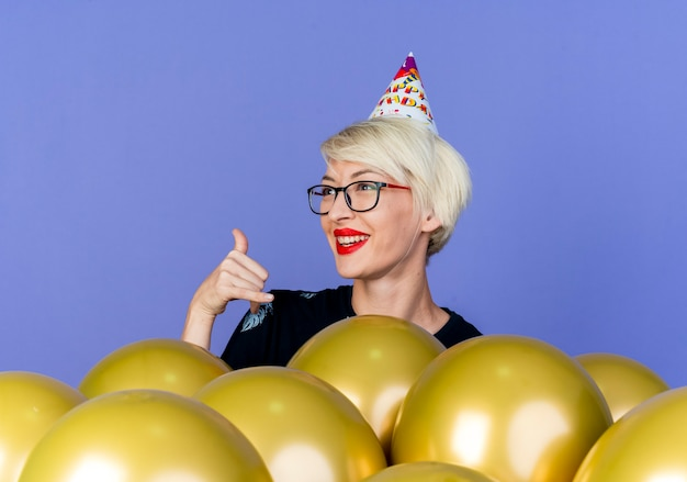 Alegre joven rubia fiestera con gafas y gorro de cumpleaños de pie detrás de globos mirando al lado haciendo gesto suelto aislado sobre fondo púrpura