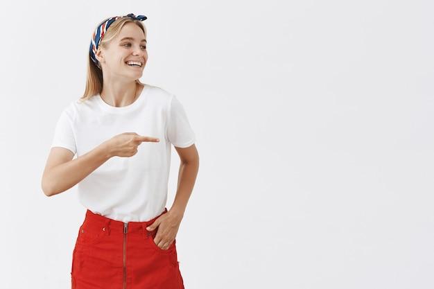 Alegre joven rubia sonriente posando contra la pared blanca