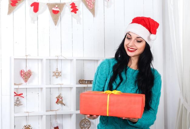 Alegre joven sentada en el interior de año nuevo vestida con sombrero de santa claus con caja de regalo roja.
