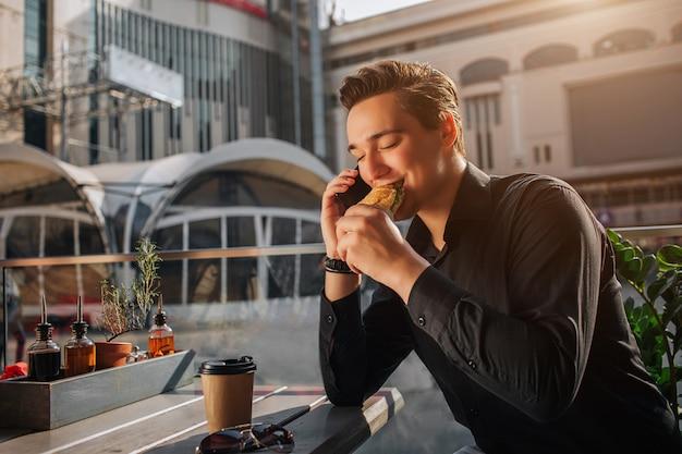 Alegre joven sentarse a la mesa afuera y comer rollo salado. mantiene los ojos cerrados. guy habla por teléfono. está soleado afuera.
