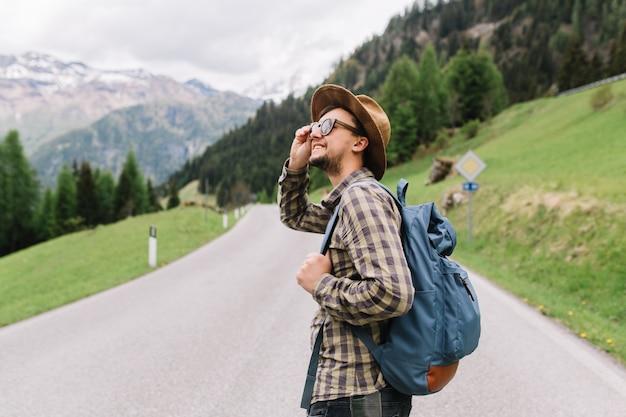Alegre joven con sombrero marrón claro y camisa a cuadros caminando por la carretera entre campos y hablando por teléfono