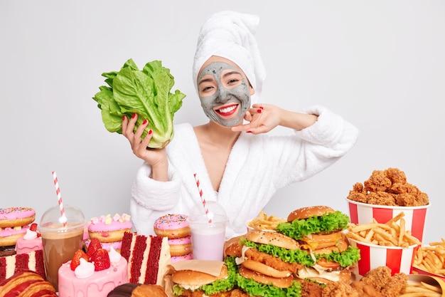 Alegre joven soñadora se somete a procedimientos de belleza en casa parece felizmente lejos sostiene lechuga romana verde