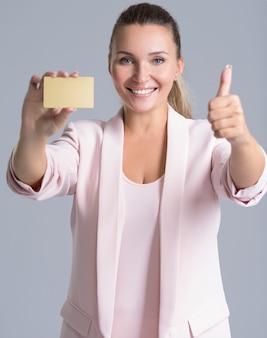 Alegre joven sorprendida emocionada con tarjeta de crédito y pulgar hacia arriba sobre blanco