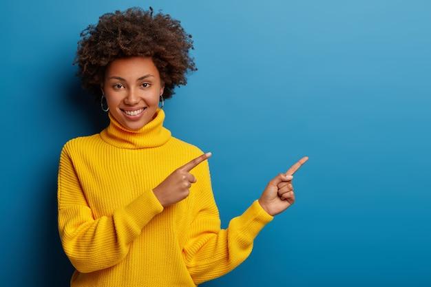 Alegre joven en suéter amarillo apunta a un lado en el espacio de la copia, muestra un anuncio fresco contra el fondo azul.