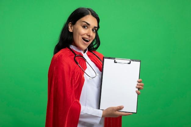 Alegre joven superhéroe vestida con bata médica con estetoscopio sosteniendo el portapapeles aislado en verde