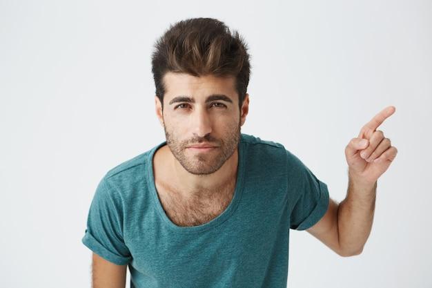 Alegre joven varón caucásico con camiseta azul con elegante corte de pelo apuntando con su dedo índice hacia un lado en blanco en blanco copia espacio en la pared, lo que indica algo extraordinario