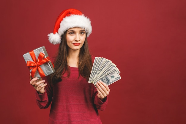 Alegre joven vestida de suéter rojo con sombrero de navidad de pie sosteniendo dinero y caja de regalo sorpresa.