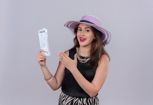 Alegre joven viajera vistiendo camiseta negra con sombrero sosteniendo boletos y apunta a boletos en la pared blanca