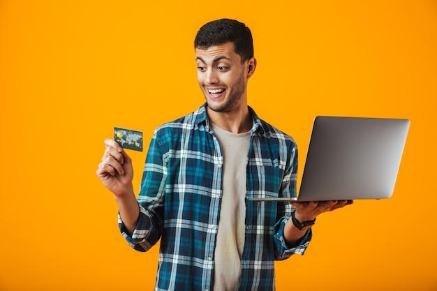 Alegre joven vistiendo camisa a cuadros se encuentran aisladas sobre fondo naranja, sosteniendo el ordenador portátil, mostrando una tarjeta de crédito de plástico