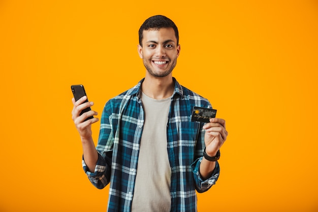 Alegre joven vistiendo camisa a cuadros se encuentran aisladas sobre fondo naranja, sosteniendo el teléfono móvil, mostrando una tarjeta de crédito de plástico