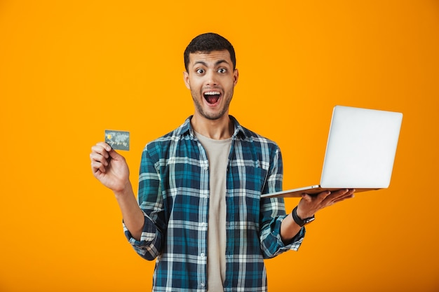 Alegre joven vistiendo camisa a cuadros que se encuentran aisladas sobre fondo naranja, usando una computadora portátil, mostrando una tarjeta de crédito de plástico