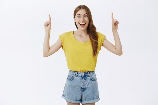 Alegre jovencita apuntando con el dedo hacia arriba, mostrando publicidad