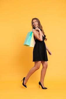 Alegre jovencita en vestido negro con bolsas de compras.