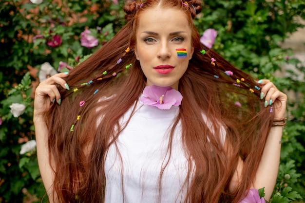Alegre lesbiana con lgbt rainbow en su rostro posando en la naturaleza
