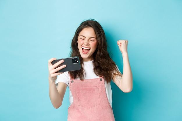 Alegre linda chica ganando en videojuegos en línea en un teléfono inteligente, haciendo puñetazos y gritando sí con alegría, de pie sobre fondo azul y triunfando.