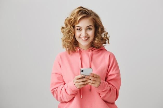 Alegre linda chica de pelo rizado mediante teléfono móvil y sonriendo