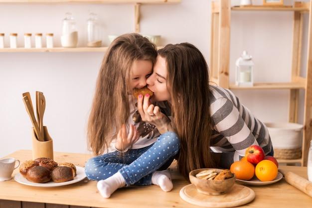 Alegre madre e hija en la cocina preparando el desayuno. comen galletas, juegan panqueques y se ríen.