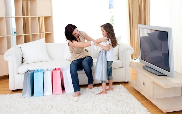 Alegre madre y su hija en casa después de ir de compras