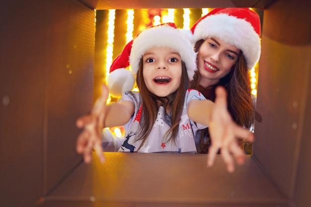 Alegre mamá y su hija linda niña abriendo un regalo de navidad