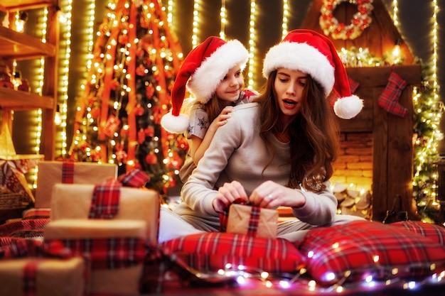 Alegre mamá y su hija linda niña intercambiando regalos. los padres y los niños pequeños se divierten cerca del árbol en el interior. familia amorosa con regalos en la sala de navidad.