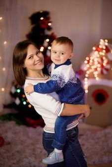 Alegre mamá y su hijo lindo niño divirtiéndose cerca de un árbol en el interior