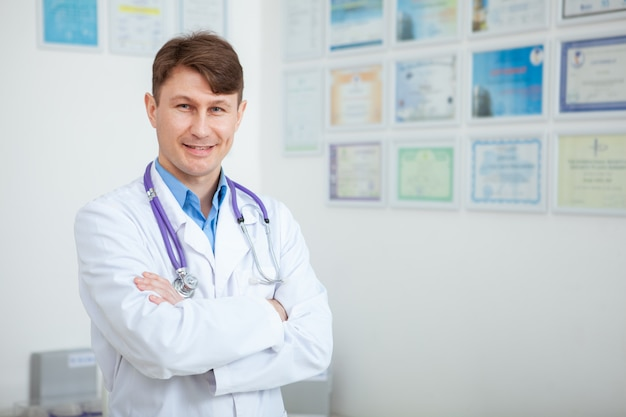 Alegre médico varón maduro sonriendo posando con orgullo en su clínica, espacio de copia