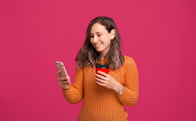 Alegre moda joven mirando su teléfono inteligente y sosteniendo la taza de café