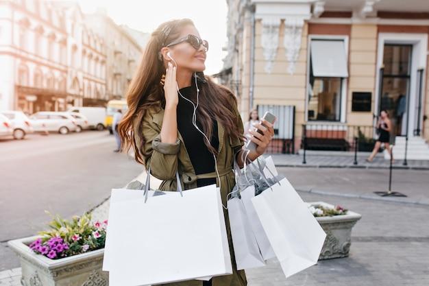Alegre modelo femenino de pelo largo con bolsas mirando a otro lado con una sonrisa